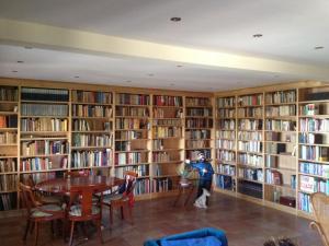 Librería madera con forma de L a medida del hueco llena de libros