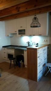 Cocina puertas blanco pvc con Encimera granito negro y madera